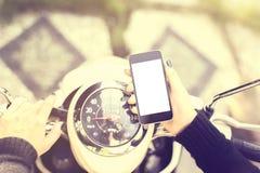 Muchacha en una moto con un teléfono celular en blanco Foto de archivo libre de regalías