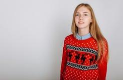 Muchacha en una Navidad o un suéter del Año Nuevo en el estudio, lugar para el humor de la Navidad del texto Imagenes de archivo