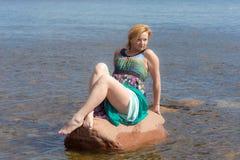 Muchacha en una piedra en el agua imágenes de archivo libres de regalías