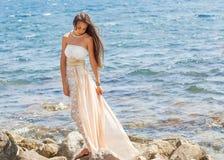 Muchacha en una piedra Mar u océano de la playa imagen de archivo