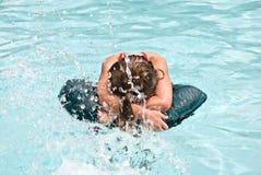Muchacha en una piscina que es salpicada Imagen de archivo libre de regalías