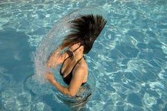 Muchacha en una piscina que lanza el pelo mojado Foto de archivo
