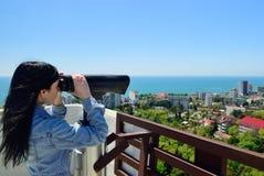 Muchacha en una plataforma de la visión que mira a través de los prismáticos el CIT Imágenes de archivo libres de regalías