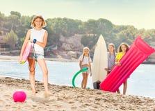 Muchacha en una playa con el grupo de amigos para arriba para la diversión Imágenes de archivo libres de regalías