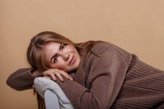 Muchacha en una reclinación caliente del suéter Fotos de archivo