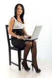 Muchacha en una silla con el ordenador Imágenes de archivo libres de regalías