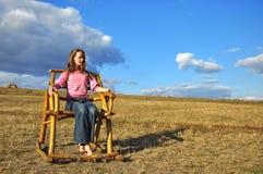 Muchacha en una silla de madera Imagen de archivo libre de regalías