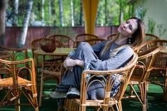 Muchacha en una silla de mimbre en sol de la última hora de la tarde Imagen de archivo