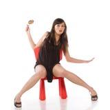 Muchacha en una silla del juguete Fotos de archivo libres de regalías