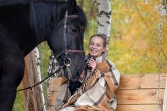 Muchacha en una tela escocesa con un caballo negro en el otoño debajo de un árbol de abedul en un banco Fotografía de archivo