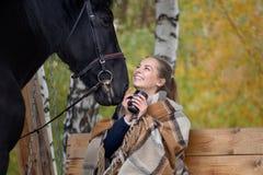 Muchacha en una tela escocesa con un caballo negro en el otoño debajo de un árbol de abedul en un banco Imagen de archivo