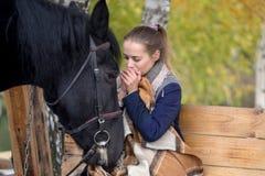 Muchacha en una tela escocesa con un caballo negro en el otoño debajo de un árbol de abedul en un banco Imágenes de archivo libres de regalías