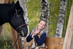Muchacha en una tela escocesa con un caballo negro en el otoño debajo de un árbol de abedul en un banco Imagenes de archivo