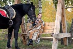 Muchacha en una tela escocesa con un caballo negro en el otoño debajo de un árbol de abedul en un banco Fotos de archivo