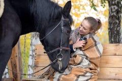 Muchacha en una tela escocesa con un caballo negro en el otoño debajo de un árbol de abedul en un banco Imagen de archivo libre de regalías