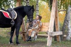 Muchacha en una tela escocesa con un caballo negro en el otoño debajo de un árbol de abedul en un banco Fotografía de archivo libre de regalías