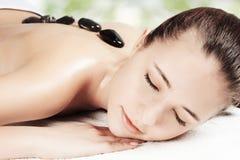 Muchacha en una terapia de piedra, masaje de piedra caliente Foto de archivo
