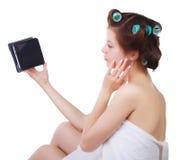 Muchacha en una toalla de baño y bigudíes de pelo con la tableta en sus manos fotos de archivo