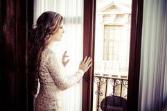 Muchacha en una ventana Imagenes de archivo