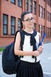 Muchacha en uniforme escolar con la mochila que se coloca en campus Foto de archivo