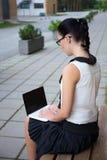Muchacha en uniforme escolar usando el ordenador portátil en campus Fotos de archivo
