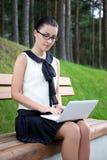 Muchacha en uniforme escolar usando el ordenador portátil en parque o campus Fotografía de archivo libre de regalías