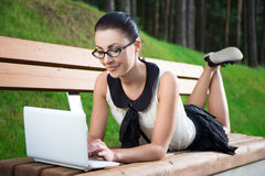 Muchacha en uniforme escolar usando el ordenador portátil que miente en banco en parque Foto de archivo libre de regalías