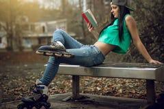 Muchacha en vaqueros que lee un libro en banco Imagenes de archivo