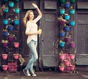 Muchacha en vaqueros y zapatillas de deporte con una taza amarilla que agita cerca de la pared con las flores outdoor Fotografía de archivo