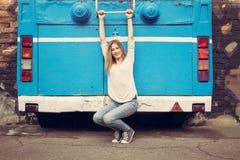 Muchacha en vaqueros y zapatillas de deporte que presentan cerca del autobús viejo outdoor Foto de archivo libre de regalías