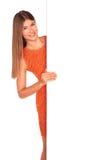 Muchacha en vestido anaranjado detrás del tablero blanco Imágenes de archivo libres de regalías