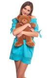 Muchacha en vestido azul con el aislante del oso de peluche en el fondo blanco Fotos de archivo