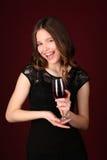 Muchacha en vestido con el vino Cierre para arriba Fondo rojo oscuro Fotografía de archivo libre de regalías