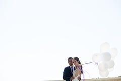 Muchacha en vestido de boda y husbad con impulsos en manos Imagen de archivo libre de regalías