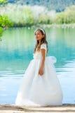 Muchacha en vestido de la comunión en el lago. Fotografía de archivo