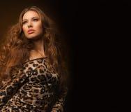 Muchacha en vestido del leopardo y zapatos negros en fondo marrón Fotografía de archivo
