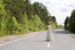 Muchacha en vestido en el camino Imagen de archivo