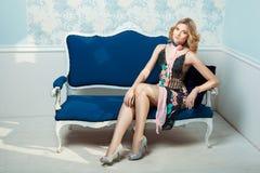 Muchacha en vestido en el sofá Imagenes de archivo
