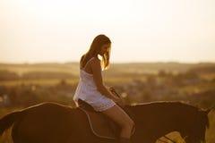 Muchacha en vestido en un caballo Foto de archivo