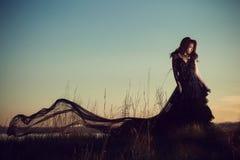 Muchacha en vestido largo en fondo de la puesta del sol Imagen de archivo
