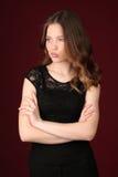 Muchacha en vestido negro con los brazos cruzados Cierre para arriba Fondo rojo oscuro Imagen de archivo libre de regalías
