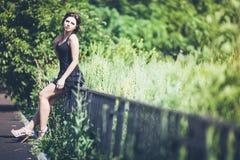 Muchacha en vestido negro en la cerca Fotografía de archivo libre de regalías