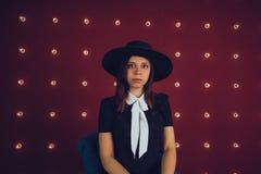 Muchacha en vestido negro y el sombrero negro que presentan en fondo rojo fotos de archivo libres de regalías