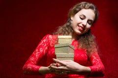Muchacha en vestido rojo con la caja de regalo Imagen de archivo libre de regalías