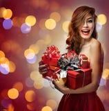 Muchacha en vestido rojo con los regalos Foto de archivo