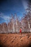 Muchacha en vestido rojo en arboleda del abedul Fotografía de archivo