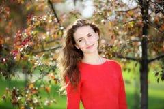 Muchacha en vestido rojo en el jardín Imagenes de archivo