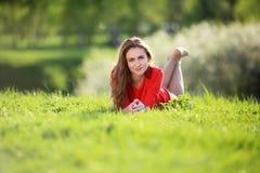 Muchacha en vestido rojo en el jardín Fotos de archivo