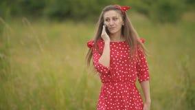 Muchacha en vestido rojo que habla en el tel?fono almacen de metraje de vídeo