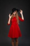 muchacha en vestido rojo y sombrero negro Fotografía de archivo